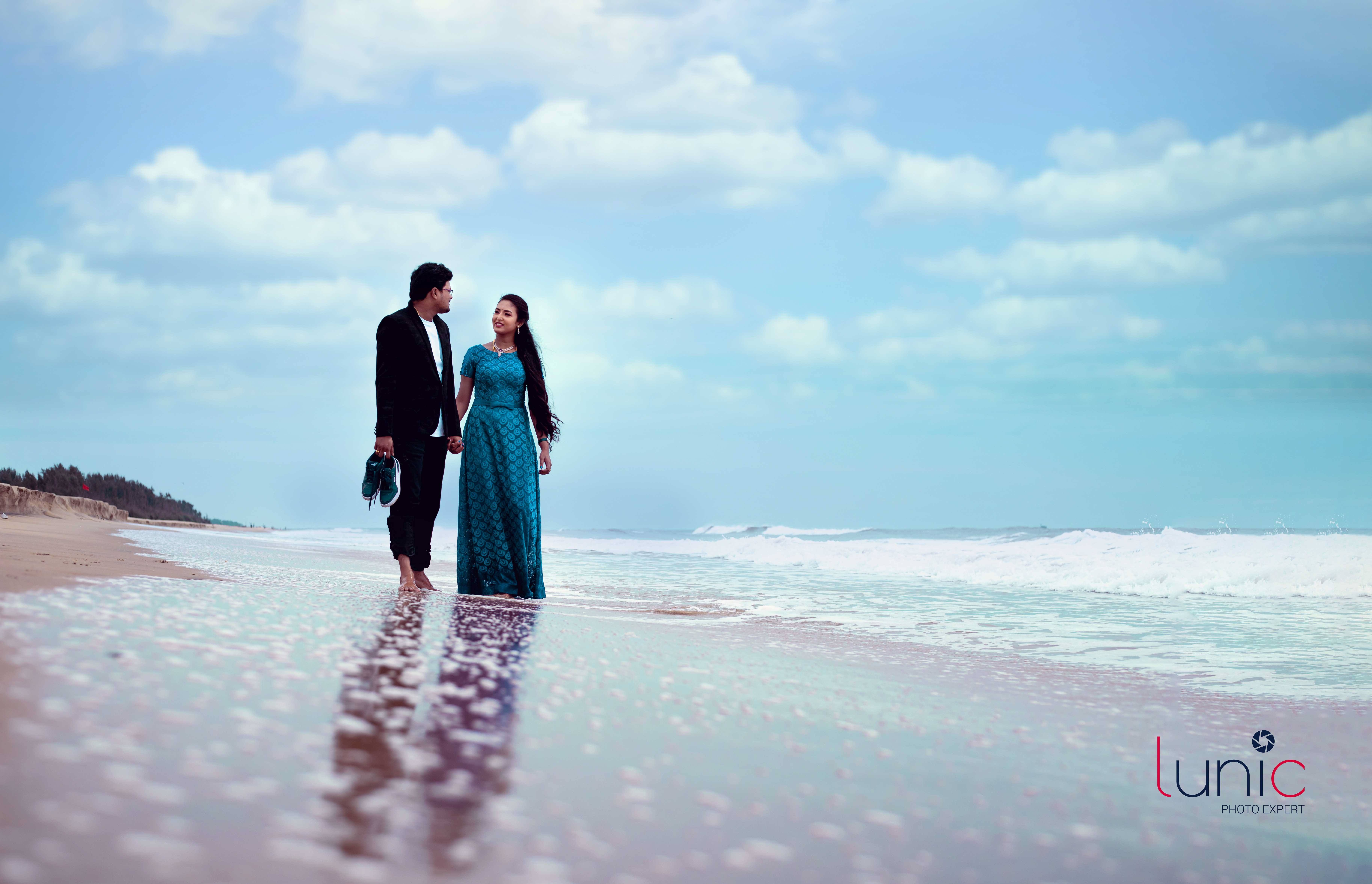 couple playing at beach during post wedding shoot